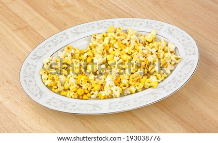 An oval platter of popcorn on a dining room table. - stock photo
