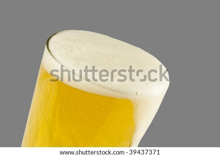An overflowing glass of beer against a 50% gray background for easy clipping path selection - stock photo