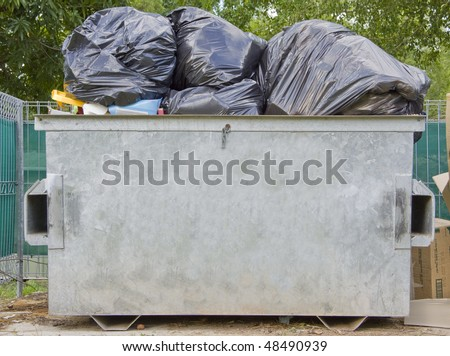 An overfull dumpster bin with clipping path - stock photo