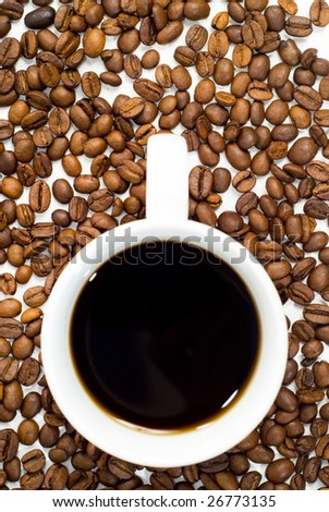 An overhead view of a cup of coffee and beans - stock photo