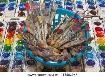 An overhead view of old, used artist paintbrushes standing in a container against a background of colorful watercolor pans - stock photo