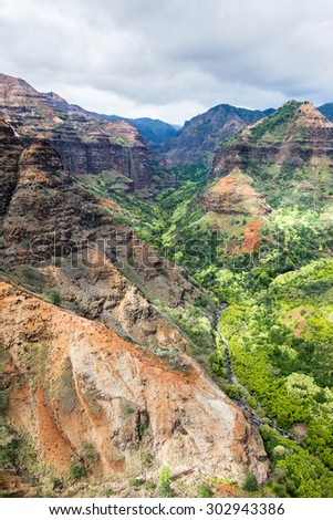 An overlook of Waimea canyon during a partly cloudy day shows the colorful, textured patterns of the rocky terrain. - stock photo