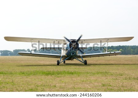AN2 plane with the engine running and rotating screw before take off  from the field aerodrome. Summer day in the sky overcast. - stock photo