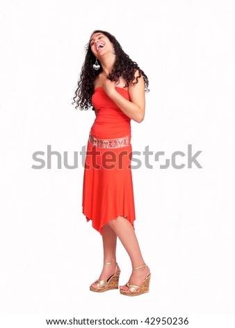 An pretty young girl with long dark hair in an nice red dress is standing and smiling on white background. - stock photo