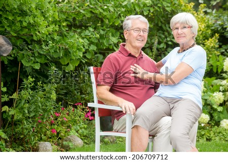 An romantic elderly couple sitting outside, are both looking at the camera and are having fun together in a garden - stock photo