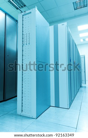 An row of racks in a commercial data center securely housing computers and servers. - stock photo