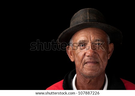 An senior man with weathered hat and features peers at the camera. - stock photo