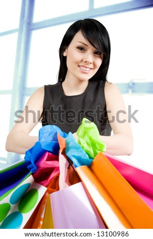 An shot of a beautiful woman carrying shopping bags in a store