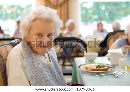 An smiling elderly woman sits down to enjoy a meal at her nursing home care center with a sunny background. - stock photo