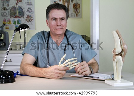 An smiling orthopedic doctor holding a skeletal model of the human hand, with a model of a human knee on his desk. - stock photo