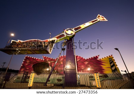 An state fair ride spinning in the dusk - stock photo