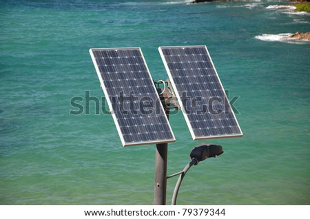 An streetlight with solar panel against sea background - stock photo