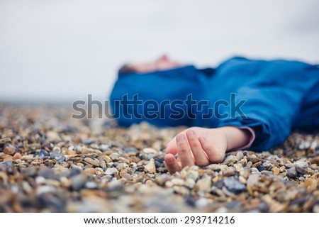 An unconscious woman is lying on a shingle beach - stock photo