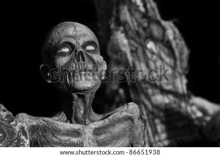 An undead monster in old style B&W, coffin in the background. - stock photo