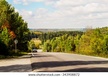 An undulating landscape with road and truck in the country. Image with selective focus - stock photo