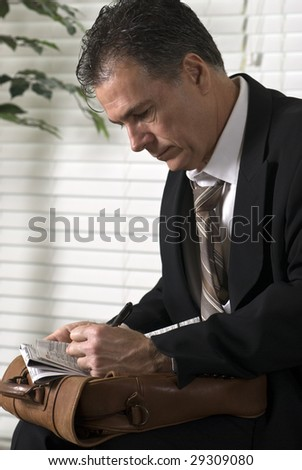 An unemployed white collar worker searching through the want ads.