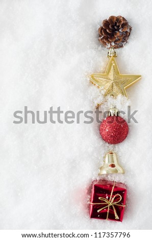 An uneven vertical line of Christmas ornaments running from top to bottom of frame, half buried in snow, on right hand side.  Copy space to left. - stock photo