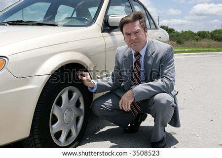An unhappy looking businessman discovering a screw in his flat tire. - stock photo