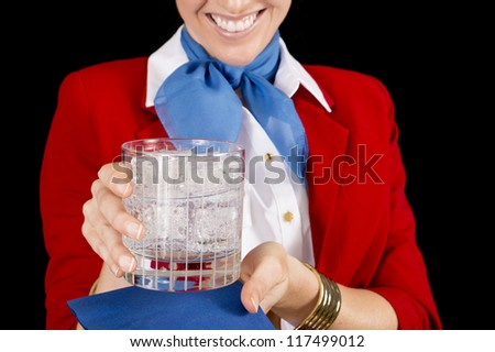 An unidentifiable flight attendant or restaurant server offering a refreshing beverage.  Focus on the drink. - stock photo