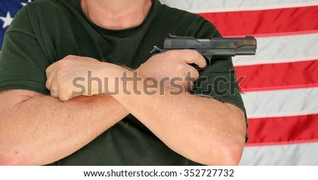 An unidentifiable person holds a loaded, and cocked pistol across his chest with an American flag background behind him. 2nd amendment rights. self protection. security of life and property. - stock photo
