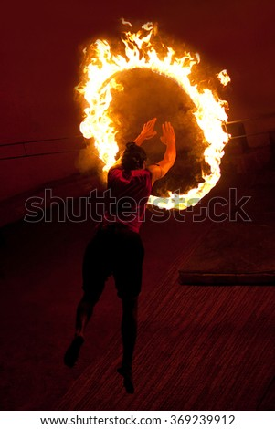 An unidentified kalaripayattu master jumping through fire ring during Kalaripayattu martial arts demonstration in Kerala, India. Kalaripayattu is an ancient form of martial art of Kerala. - stock photo