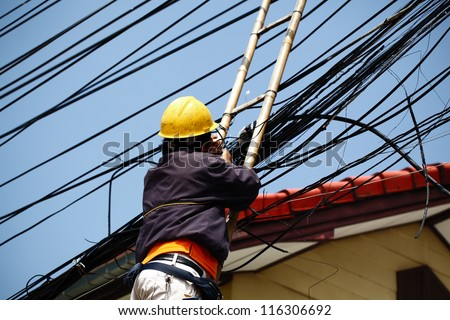 An unidentified male worker on bamboo ladder is repairing telephone line near the community. - stock photo