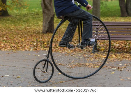 An unidentified men riding a penny-farthing bicycle in a park with fallen autumn leaves