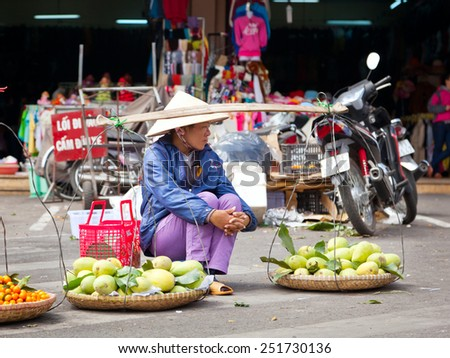 An unidentified woman sells fruit in the market, Vietnam, Dalat. February 2, 2015. Editorial image - stock photo