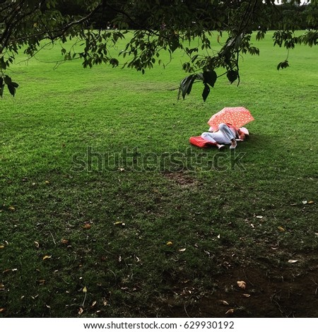 An unidentified woman sleeps on the green grass of a Tokyo park, Japan