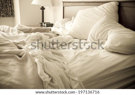 An unmade bed with white linens and a lamp in the corner. - stock photo