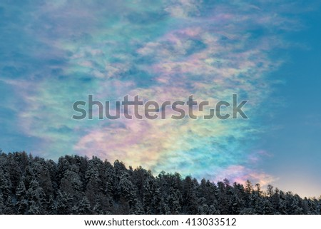 An unusual flat rainbow above trees in the Swiss Alps in mid winter. - stock photo