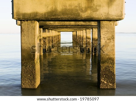 An unusual perspective from underneath the concrete base of the popular fishing pier at Lighthouse Beach on Sanibel Island, Florida, looking out over the Gulf Of Mexico. - stock photo