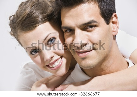 An up-close shot of a couple posing.  The female has her arms embraced around the male's neck.  They are smiling directly at the camera. Horizontally framed photo.