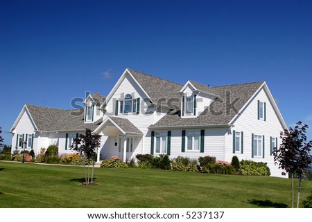 An upscale executive home surrounded by a lush green lawn. - stock photo