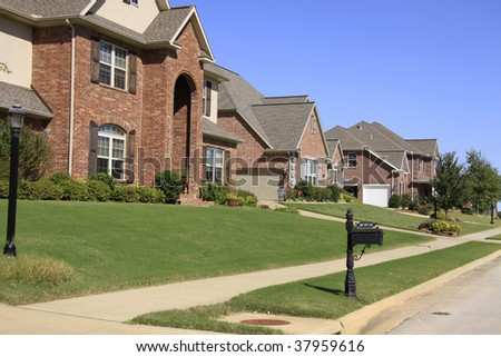 An upscale neighborhood of beautiful brick homes and landscaped yards. - stock photo