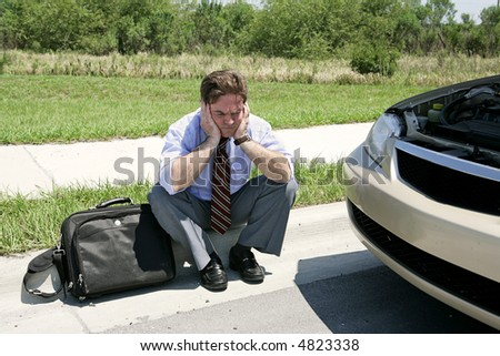 An upset businessman on the side of the road with his broken down car waiting for the auto club.