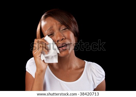 an upset woman cries and wipes her eyes with a tissue - stock photo