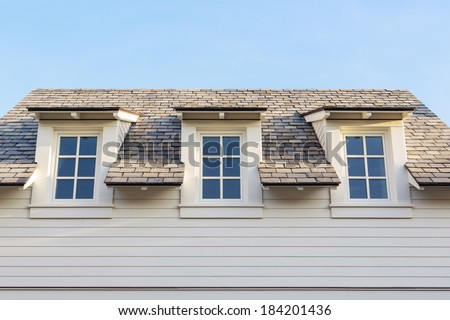 An upwards view at 3 attic windows of a white family home. The house is white siding with white trim. Roof detail can be seen, as well as a clear, blue sky.  - stock photo