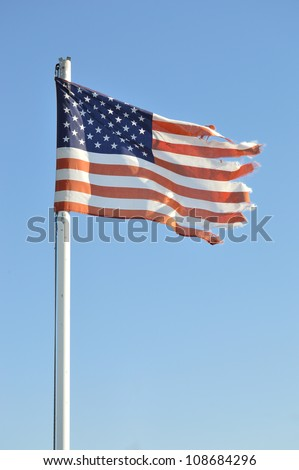 An US ragged flag torn in the sky - stock photo