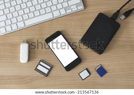 An USB Stick an external hdd, different memory cards, a modern keyboard and a smartphone with white isolated screen on a wooden desk - stock photo