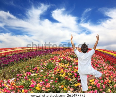 "An woman dressed in white doing yoga pose ""Tree"". Buttercups blooming garden. Farmers field with flowers grown for export sales - stock photo"
