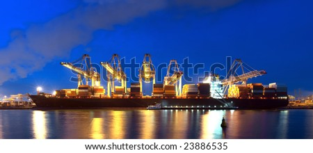 An XXXL file of a container ship being unloaded at night at a busy commercial harbour, with a small trawler moored alongside. - stock photo