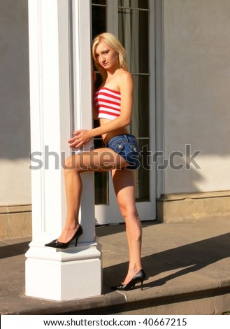 An young beautiful lady is sitting on the steps of an old mansion wearing an red and white striped top and short jeans shorts.
