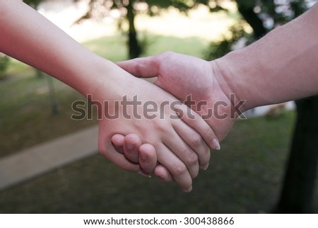 An young couple holding hands. Small depth of field.  - stock photo