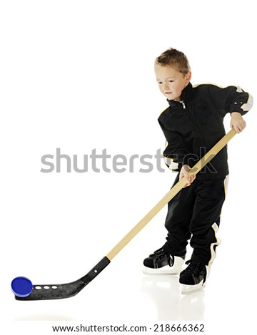 An young elementary athlete in uniform, hitting the puck with his hockey stick.  Motion blur on the puck.   On a white background. - stock photo