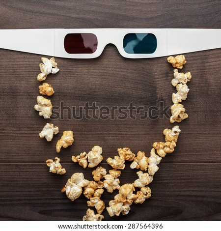 anaglyph glasses and popcorn on wooden table making bearded face - stock photo