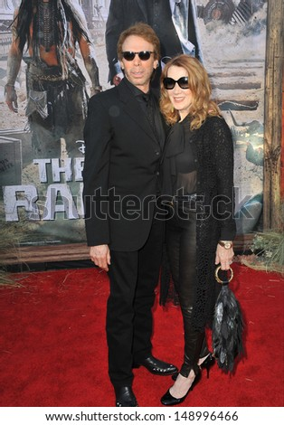 "ANAHEIM, CA - JUNE 22, 2013: Producer Jerry Bruckheimer & wife at the world premiere of his new movie ""The Lone Ranger"" at Disney California Adventure.  - stock photo"