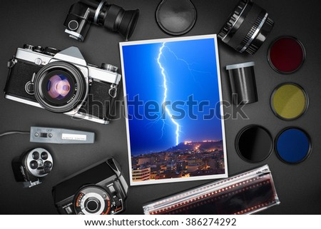 Analog SLR camera equipment around a printed photo of a lightning that strikes over the city - stock photo
