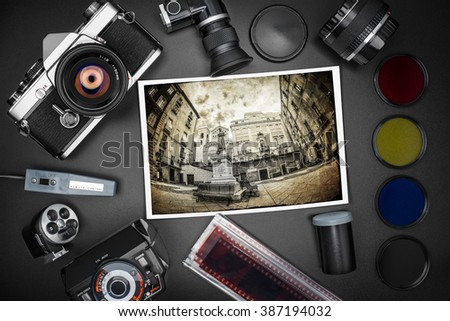 Analog SLR camera equipment around an old printed photo of a city square - stock photo