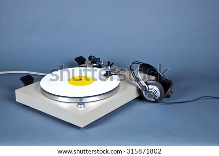 Analog Stereo Turntable Vinyl Record Player with White Disk and Headphones - stock photo